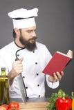 Jonge chef-kok in eenvormige lezing een recept, klaar te koken Royalty-vrije Stock Foto's