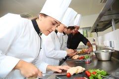 Jonge chef-koks die delicatessen voorbereiden Stock Foto's