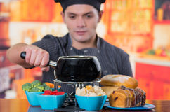 Jonge cheff die een gastronomisch Zwitsers fonduediner met geassorteerde kazen en een verwarmde pot van kaasfondue en wat voorber royalty-vrije stock foto's
