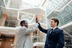 Jonge collega's die elkaar hoogte vijf geven terwijl status in een bureau stock foto's