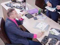Jonge collega's die in het bureau, Bespreking werken Kritovalyuta Geld stock foto's