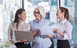 Jonge collega's en hun werkgever die samen in een bureau lachen Stock Afbeeldingen