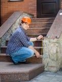 Jonge contractantarbeider die trap met het meten van band meten Stock Foto's