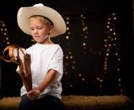 Jonge cowboyzitting op hooibaal met zijn stokpaard Royalty-vrije Stock Foto