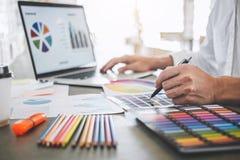 Jonge creatieve grafische ontwerper die aan van de project architecturale tekening en kleur monsters, selectie het kleuren op gra stock afbeelding