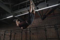 Jonge crossfitatleet die op gymnastiek- ringen slingeren die trekkracht-UPS doen bij gymnastiek Trainingoefeningen stock afbeelding