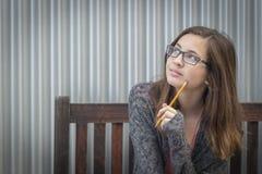 Jonge Dagdromen Vrouwelijke Student With Pencil Looking aan de Kant stock foto