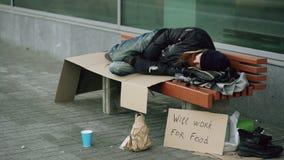 Jonge dakloze gedronken mens die aan slaap op karton op bank bij de stoep voorbereidingen treffen Stock Afbeeldingen