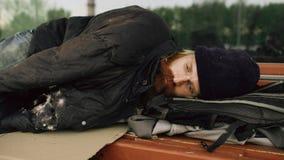 Jonge Dakloze mens die aan slaap onder jasje op bank bij de stoep proberen Royalty-vrije Stock Foto's