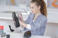 Jonge dame bespuitende schoen stock afbeelding