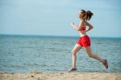 Jonge dame die bij het zonnige strand van het de zomerzand lopen workout jog stock foto