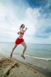Jonge dame die bij het zonnige strand van het de zomerzand lopen workout jog stock foto's