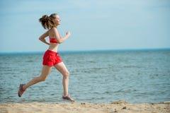 Jonge dame die bij het zonnige strand van het de zomerzand lopen workout jog stock afbeelding
