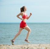 Jonge dame die bij het zonnige strand van het de zomerzand lopen workout jog stock fotografie