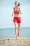 Jonge dame die bij het zonnige strand van het de zomerzand lopen workout jog royalty-vrije stock afbeelding
