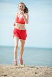 Jonge dame die bij het zonnige strand van het de zomerzand lopen workout jog royalty-vrije stock foto's