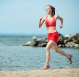 Jonge dame die bij het zonnige strand van het de zomerzand lopen workout jog royalty-vrije stock afbeeldingen