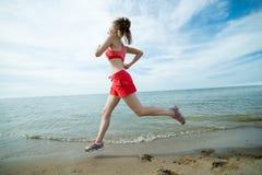 Jonge dame die bij het zonnige strand van het de zomerzand lopen workout jog stock afbeeldingen