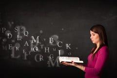 Jonge dame die een boek met alfabetbrieven lezen Stock Foto's