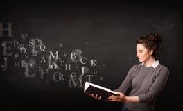Jonge dame die een boek met alfabetbrieven lezen stock foto