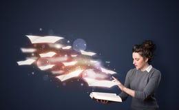 Jonge dame die een boek met vliegende bladen lezen die uit B komen stock afbeeldingen