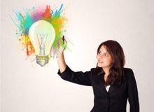 Jonge dame die een kleurrijke gloeilamp met kleurrijke plonsen trekken Stock Afbeelding