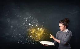Jonge dame die een magisch boek lezen stock afbeeldingen