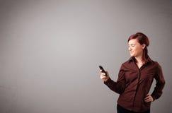 Jonge dame die en een telefoon met exemplaarruimte bevinden zich houden Royalty-vrije Stock Foto's
