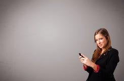 Jonge dame die en een telefoon met exemplaarruimte bevinden zich houden Stock Foto