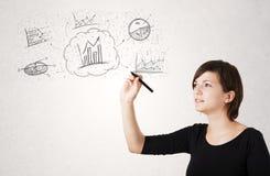 Jonge dame die financiële grafiekpictogrammen en symbolen schetsen Stock Foto