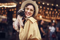Jonge dame die gelukkig terwijl het drukken van puppy aan haar wang kijken stock foto