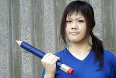Jonge dame die groot potlood houdt Stock Foto