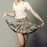 Jonge dame die haar korte rok opheffen stock afbeeldingen
