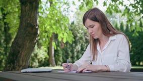 Jonge dame die in het park werken stock foto's