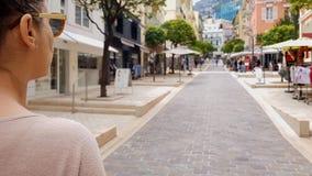 Jonge dame die langs straat met winkels lopen, die verkoop, Europese stad zoeken royalty-vrije stock fotografie