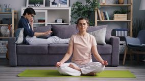 Jonge dame die in lotusbloempositie mediteren terwijl kerel die op telefoon spreken die laptop met behulp van stock footage