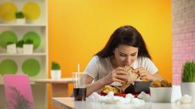 Jonge dame die misselijkheid voelen terwijl het proeven van snel voedselhamburger, ongezonde voeding stock videobeelden