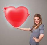 Jonge dame die mooi 3d rood hart houden Stock Afbeeldingen