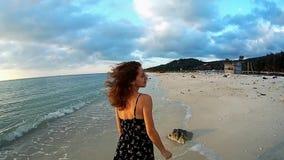 Jonge dame die op het strand bij zonsondergang lopen stock footage