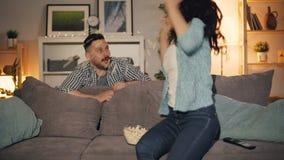 Jonge dame die op TV letten etend popcorn wanneer de echtgenoot het springende lachen bang maakt stock videobeelden