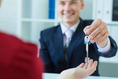 Jonge dame die sleutels van mannelijke makelaar in onroerend goed nemen tijdens vergadering Stock Afbeeldingen