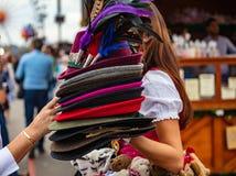 Jonge dame die in Tirools kostuum een stapel traditionele hoeden houden, Oktoberfest, München, Duitsland stock foto