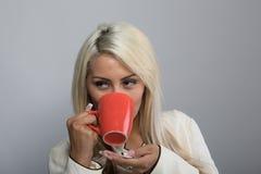 Jonge dame die van haar warme koffie genieten Stock Foto's