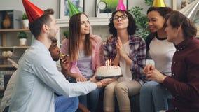 Jonge dame die wens blazende kaarsen op verjaardagscake maken bij partij met vrienden stock video