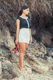 Jonge dame die zich op een rots bevinden Stock Foto's