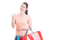 Jonge dame dragende het winkelen zakken en het tonen van nummer drie Stock Afbeeldingen