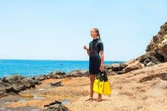 Jonge dame in het duiken kostuum met peddels die zich op rotskust bevinden stock afbeeldingen