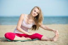 Jonge dame het praktizeren yoga Training dichtbij oceaan overzeese kust Stock Afbeelding