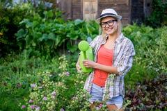 Jonge dame met glazen en hoed die groene gieter houden royalty-vrije stock foto