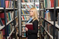 Jonge dame met los lang blond haar die en twee B bevinden zich houden Stock Afbeelding